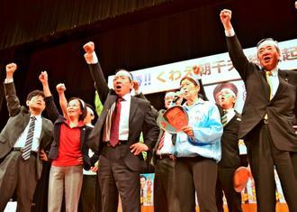 総決起大会で支持者とガンバロー三唱で気勢を上げる桑江朝千夫氏(左から3人目)=12日、沖縄市民会館