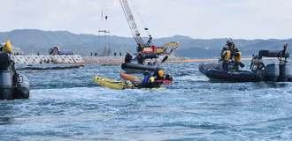 カヌーでフロートを越えて海上保安官に拘束される市民ら。奥では「K8」護岸工事が進む=2日午前、名護市辺野古