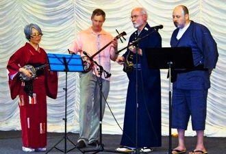 ステージで三線を披露する(左から)野崎まはぎさん、クレッグ・ホイットさん、ジャン・ジョスリンさん、ボーカルのエリック・コーペンさん=アトランタ市郊外