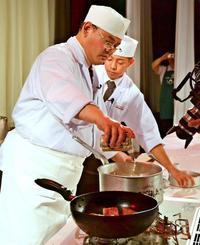 煮込み料理でオリオンビールを鍋に注ぐ城野智彦さん(手前)と新川光輝さん=21日、西原町・エリスリーナ西原ヒルズガーデン