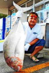 糸満海岸で117・5センチ、17・75キロのロウニンアジを釣った宮良祐さん=25日