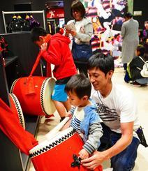 太鼓をたたいてエイサー体験を楽しむ親子連れ=25日、沖縄市上地・エイサー会館
