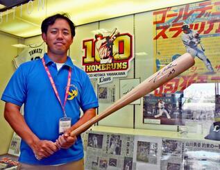 山川穂高選手の活躍を伝える記事の前で贈られたバットを握り「3年連続本塁打王に」とエールを送る大城将暉さん=29日、沖縄セルラーパーク那覇