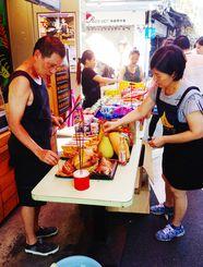 中元節に合わせて「好兄弟」の供養を行う人たち=5日、台北市龍泉街