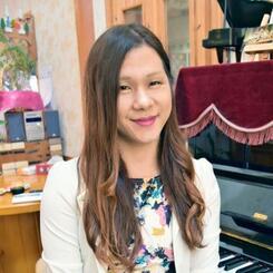 長年使っているピアノの前で笑顔を見せる下里豪志さん=南風原町本部の自宅