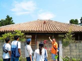 大宜味村喜如嘉の古民家を観光客に案内するオクマ プライベートビーチ&リゾートの大山章さん(右)(同ホテル提供)