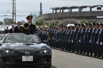オープンカーに乗って視閲する池田克史本部長=12日、北谷町営駐車場