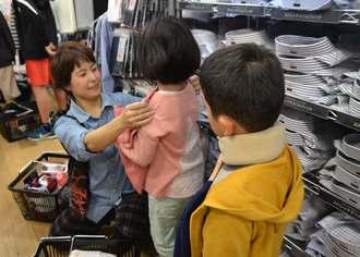 子どもたちと衣類を選ぶ園の職員=27日、宜野湾市・ユニクロはにんす宜野湾店