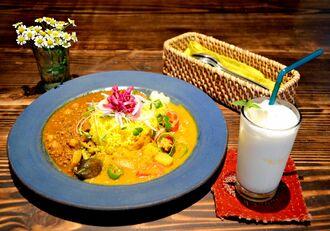 カレー2種盛りは千円(税込み)。ランチタイムはミニラッシーやアイスコーヒーなどドリンクが付く。写真はポークキーマカレーと旬の野菜カレー