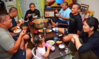 小濱寿監督(左)の自宅では毎晩、食卓を全員で囲み、会話も弾む=沖縄市