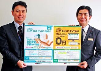 インターネットバンキングのサービス拡充をPRする川上部長(右)と亀島健司調査役=3日、沖縄タイムス社