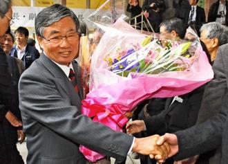 退任式を終え、職員の花道を通る稲嶺進氏=7日、名護市役所