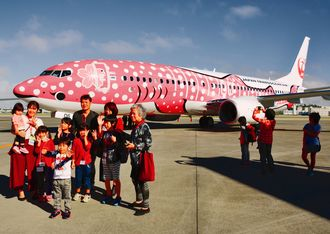 新しいジンベエジェットを前に記念撮影をする子どもら=24日、那覇空港