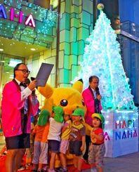 玉の子保育園の園児らのカウントダウンに合わせてライトアップされたクリスマスツリー=24日、那覇市のハピナハ