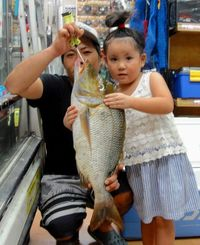 北谷海岸で63.5センチ、3.5キロのタマンを釣った玉城俊希さん(左)=9日