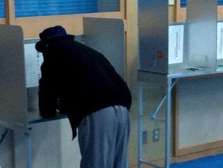 投票する男性=24日午前、宜野湾市