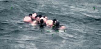 (上)転覆した漁船付近で漂流する人たち