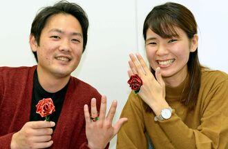 園児たちが折り紙で作った指輪を手に笑顔の吉原愛香さん(右)と京亮さん=26日、那覇市