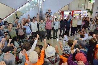 訪米出発前に支援者とともにガンバロー三唱で気勢を上げる翁長雄志知事(中央)ら=27日午前11時11分、那覇空港