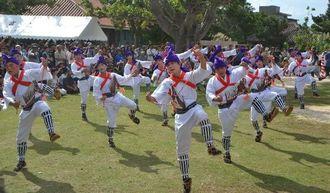 左右に力強く飛ぶ「馬乗者(んまぬしゃ)」を披露する青年たち=竹富島、世持御嶽前広場