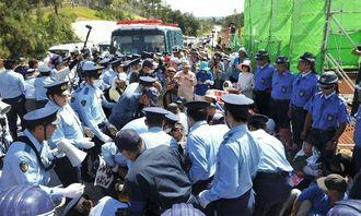 工事関係者の車両を阻止しようとゲート前に座り込み、警察官に強制排除される市民ら=29日午前9時47分、名護市辺野古