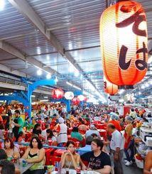 週末のフェイラ(公設市場)には数千人が訪れ、熱気があふれ圧巻だ。店内には「そば」をアピールする日本風のちょうちんが見える=カンポグランデ市内