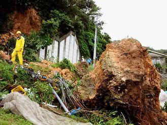 高さ3.3メートル、横幅5.5メートルの巨岩が土砂崩れで崩落。電柱を押しつぶした=11日午後1時55分、南城市知念志喜屋(又吉健次撮影)