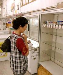 台風の影響でパンが売り切れて考え込む女性=7日午後、伊是名村のスーパー(末吉雅枝通信員撮影)