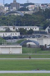 嘉手納基地で実施されたパラシュート降下訓練で、同基地内に降りる米軍兵士=9日午後4時11分、嘉手納町(下地広也撮影)