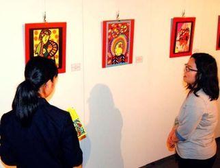 会場を訪れた高校生と絵画や小児がんについて話す岸本聡子さん(右)=17日午前、那覇市民ギャラリー