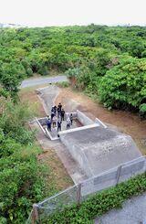 米軍普天間飛行場内でシーミーの墓掃除を終えて手を合わせる人々=11日、宜野湾市内