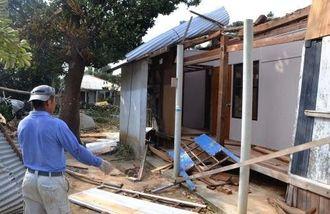 屋根が吹き飛び、半壊した住宅を見回る管理人の男性=30日、与那国町・比川地区