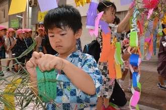 一番街七夕まつりで願いが書かれた短冊をささに飾る子どもたち=4日、沖縄市中央