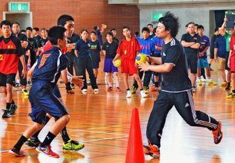 中学生対象の強化練習でドリブルして攻め込む東江太輝(右)=八重瀬町東風平体育館