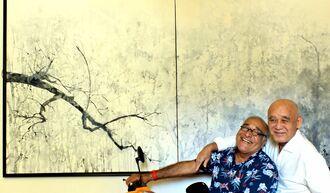 自身の大作「旅立ち」の前で笑顔を見せる与座英信さん(右)とベシャラット・マッスウドゥさん=8月30日、パリ