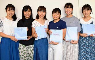 集めた支援金を託した兵庫県立長田高校2年の生徒=8日、沖縄タイムス社