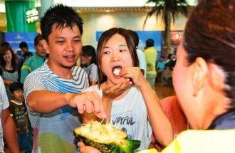 沖縄県産パインを試食する観光客=1日、那覇空港国内線ターミナルビル