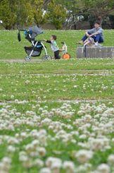 気温が上がり過ごしやすい陽気の中、公園で遊ぶ親子=15日午後、沖縄市・県総合運動公園