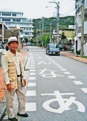 「よーんなあ」の道路標示で徐行をと呼び掛ける新垣茂信板良敷区長=与那原町同区
