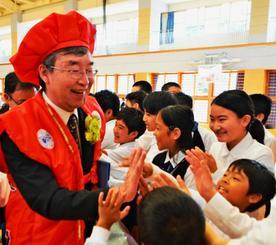 児童とハイタッチしながら花道を進む堀越泉校長(左)=名護市・東江小学校