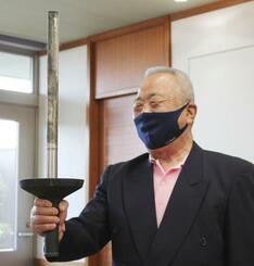 57年ぶりに1964年東京五輪の聖火リレーで使ったトーチを持つ河辺道夫さん=2日午前、愛知県豊橋市役所