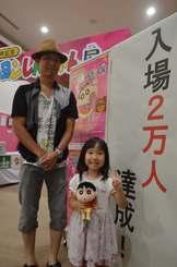 2万人目の来場者となった喜屋武愛乃香ちゃん(右)と、父の涼介さん=12日、北中城村・イオンモール沖縄ライカム