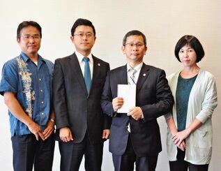 首里城再建のための寄付を託した高良祐之弁護士(右から2人目)ら=20日、沖縄タイムス社