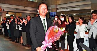 職員に拍手で出迎えられ、笑顔で登庁する松本哲治浦添市長=13日午前10時30分、浦添市役所