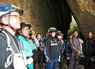 斎場御嶽の三角岩で、聖地の歴史を学ぶ自転車のライド30キロの男女ら=21日、南城市知念久手堅
