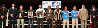 金城眞吉さんと中真茂さんを追悼する「テンカウントゴング」が鳴り響く中、黙とうするボクシング関係者=4日、沖縄県立武道館