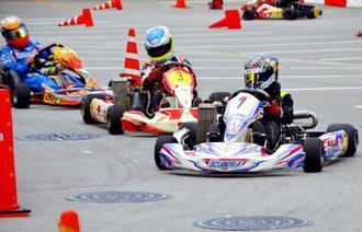 モータースポーツフェスティバルのレーシングカートで迫力ある技術を見せる出場者ら=5日、沖縄市コザ運動公園