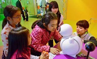 会話ができるロボットに話し掛ける来場者=沖縄市胡屋・沖縄こどもの国