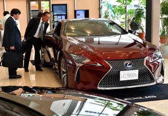 トヨタ自動車の高級ブランド「レクサス」に見入る来場者=10日、那覇市久茂地・タイムスビル1階
