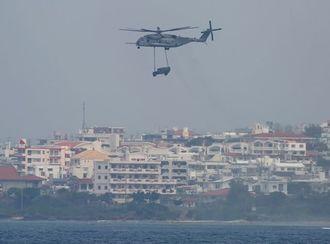 米陸軍トリイ通信施設方面から海上に向かい、車をつり下げて訓練する米軍の大型ヘリ。後ろは読谷村楚辺集落=19日午前11時16分、北谷町宮城海岸から撮影(読者提供)